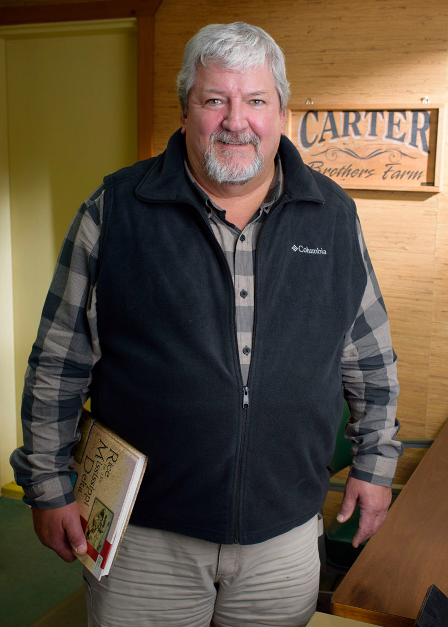 "A gray-haired man with a goatee wears a navy blue vest over a blue-checkered, long-sleeved polo and tan slacks. He stands in front of a ""Carter Brothers Farm"" sign and beside a desk with a rolodex as sun filters across the background."