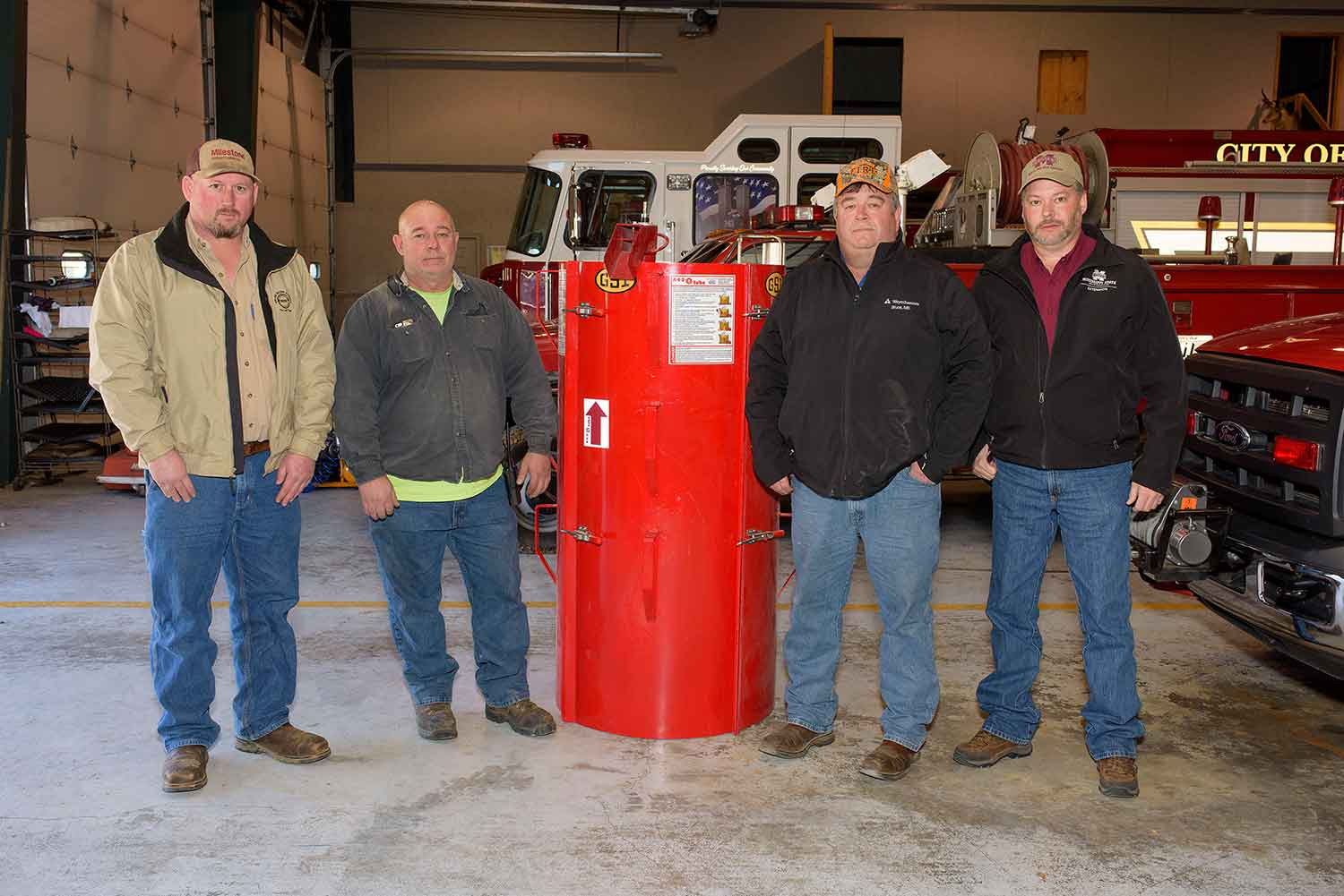 Four men stand in front of a red firetruck.