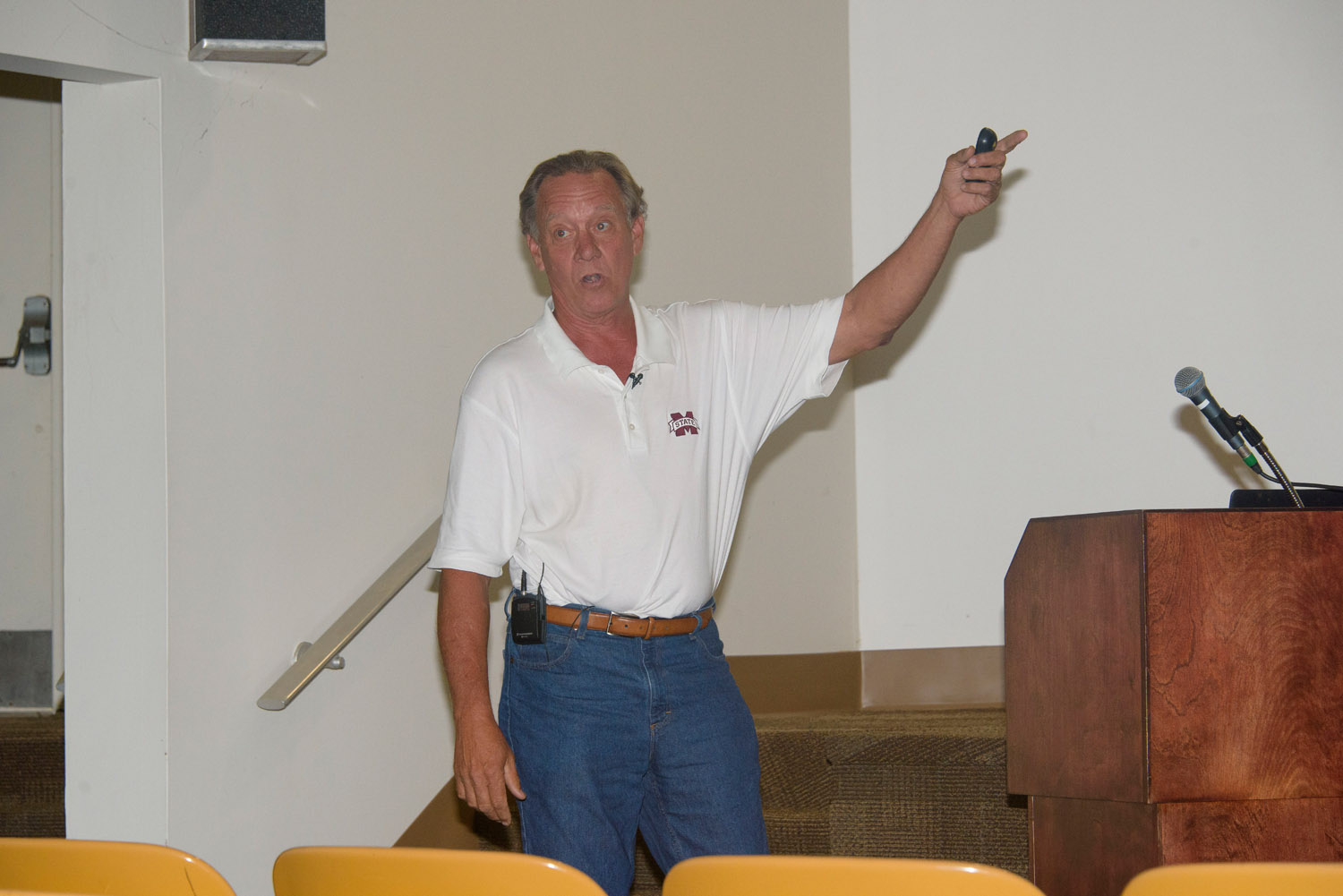 A man wears a white polo shirt with a Mississippi State University emblem on the right breast pocket, and his arm is lifted and pointing right.