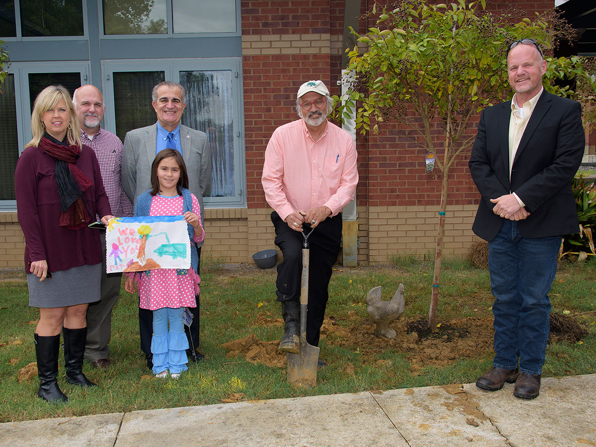 Several people stand outside of a brick building and next to a newly planted tree.