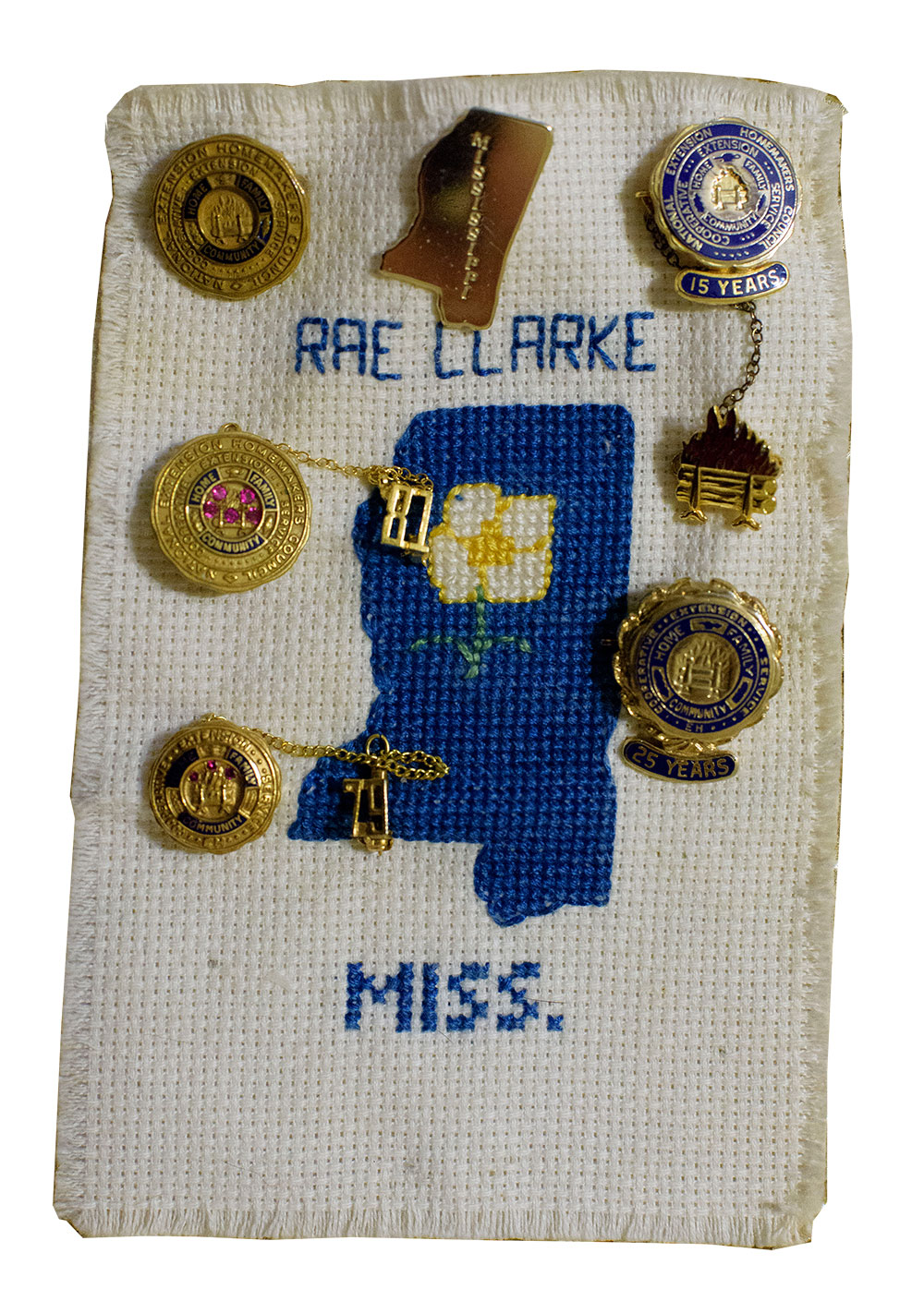 "A rectangular piece of white fabric has a blue outline of the state of Mississippi and the words ""Rae Clarke"" and ""Miss."" The fabric is decorated with several gold pins."
