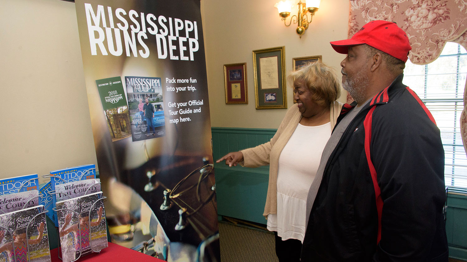 "A man wearing a red hat stands next to a smiling woman pointing at a poster that says ""Mississippi Runs Deep."""