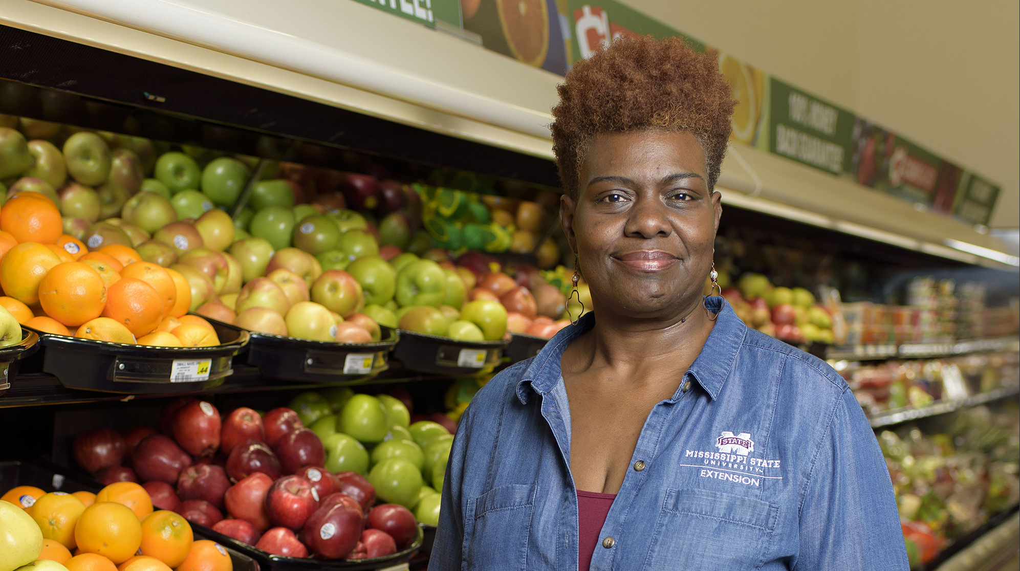 A woman stands in front of a grocery store fruit display.