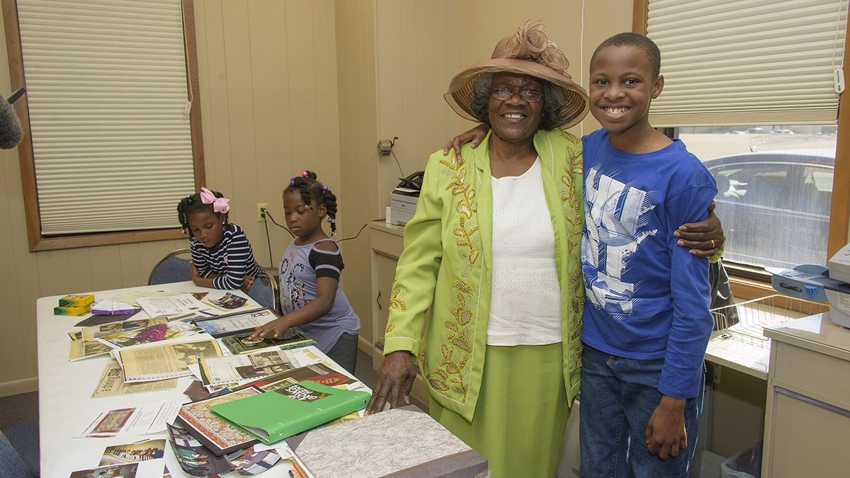 A woman in a large brown hat and a bright green jacket smiles next to a young boy wearing a dark blue shirt.