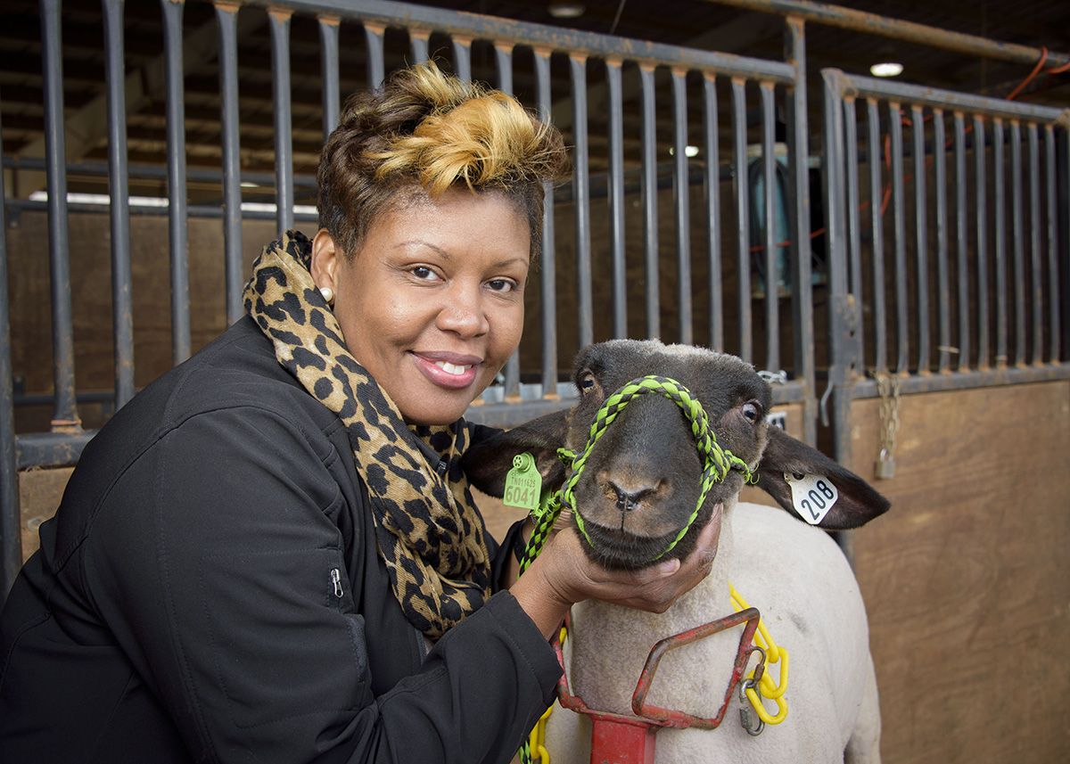 : Extension agent poses cheerfully with a goat during a local 4-H livestock show