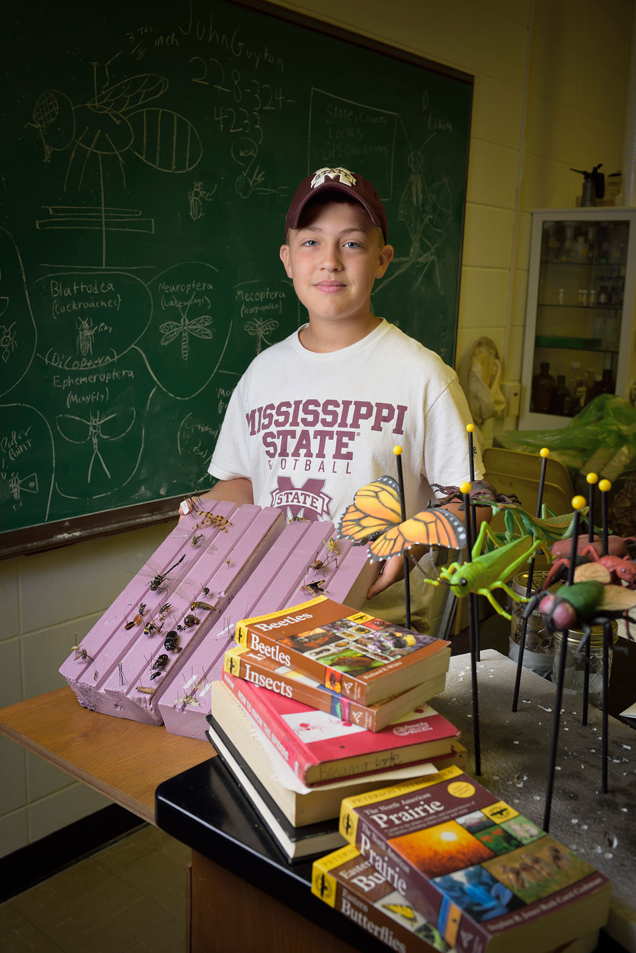 A young boy wearing a Mississippi State hat and t-shirt stands behind a stack of books and insect replicas while he holds his project, a purple piece of wood that showcases many different types of insects.