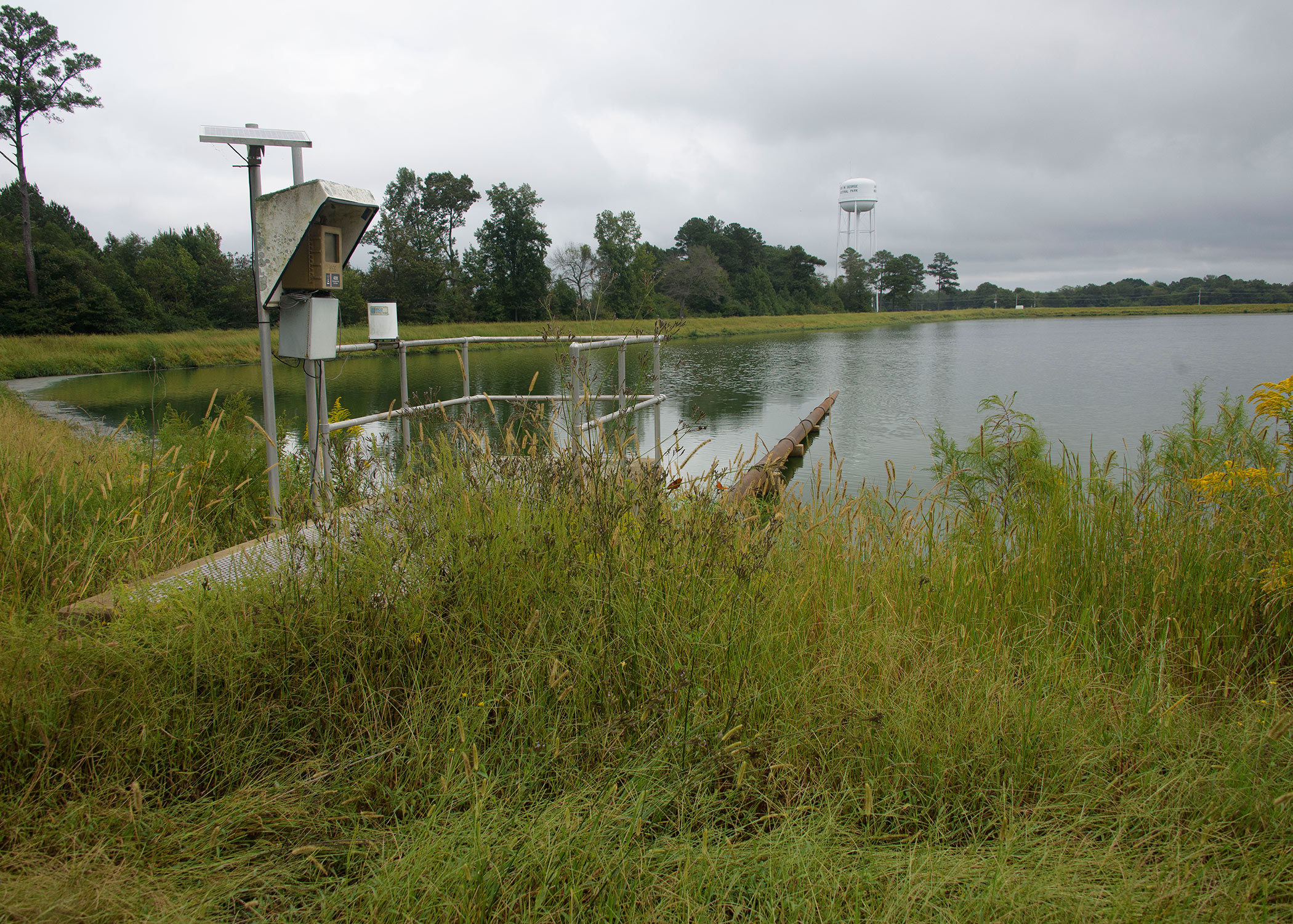 A metal structure stands in tall, green grass on the edge of a pond, where a large pipe reaches into the water from the metal structure.