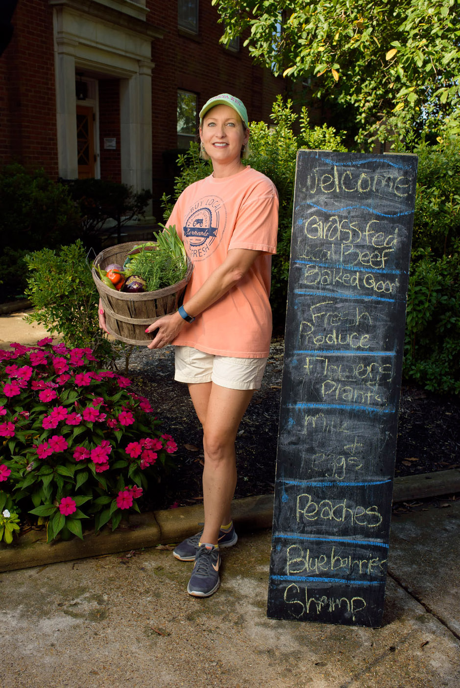 "A woman wearing a green baseball hat and wearing a peach ""Buy local, buy fresh"" T-shirt carries a basket of fruits and vegetables."