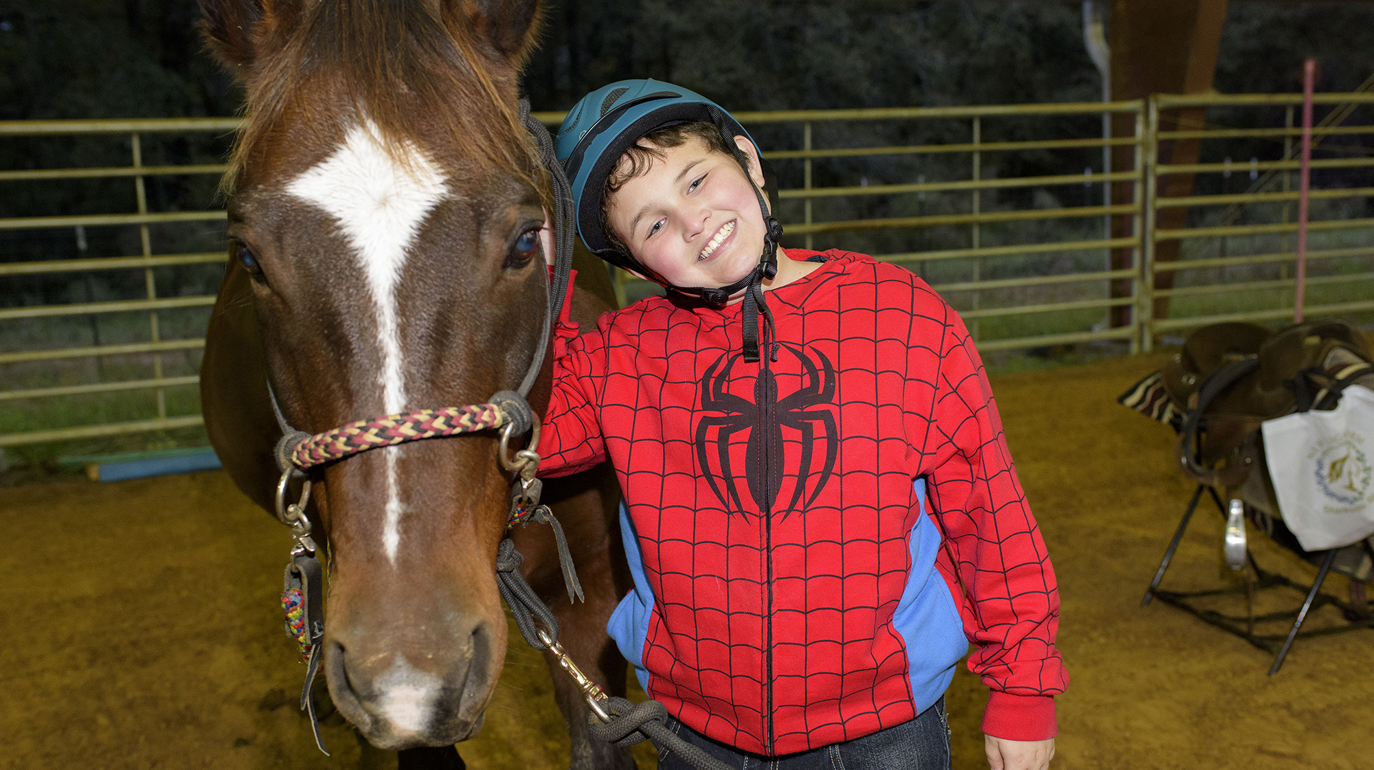 A young boy wearing a red Spiderman jacket and a blue helmet stands next to a brown and white horse.