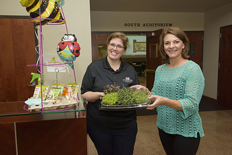 Two Extension instructors hold a tray of microgreens.