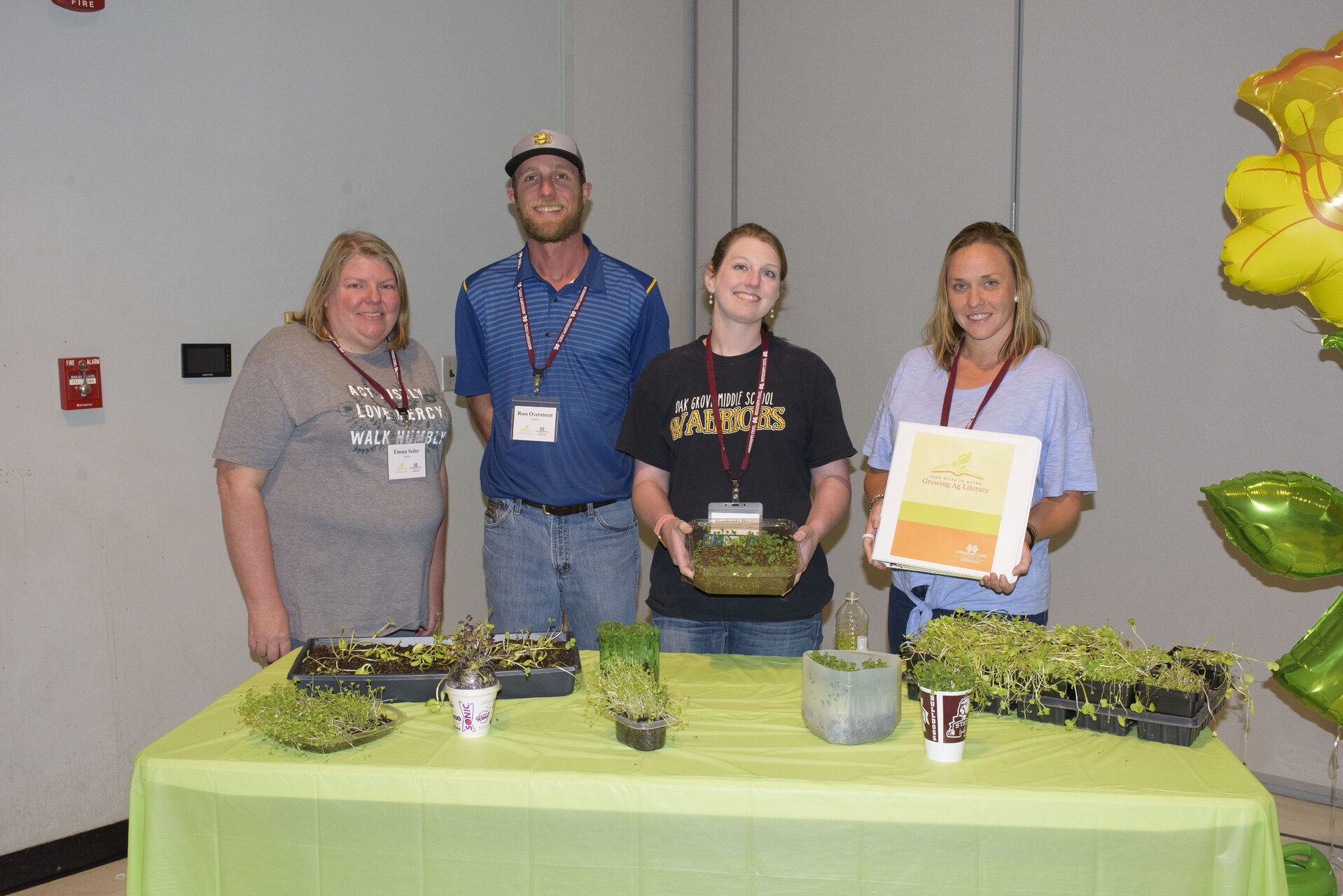 Three women and one man pose in front of a table filled with containers of microgreens