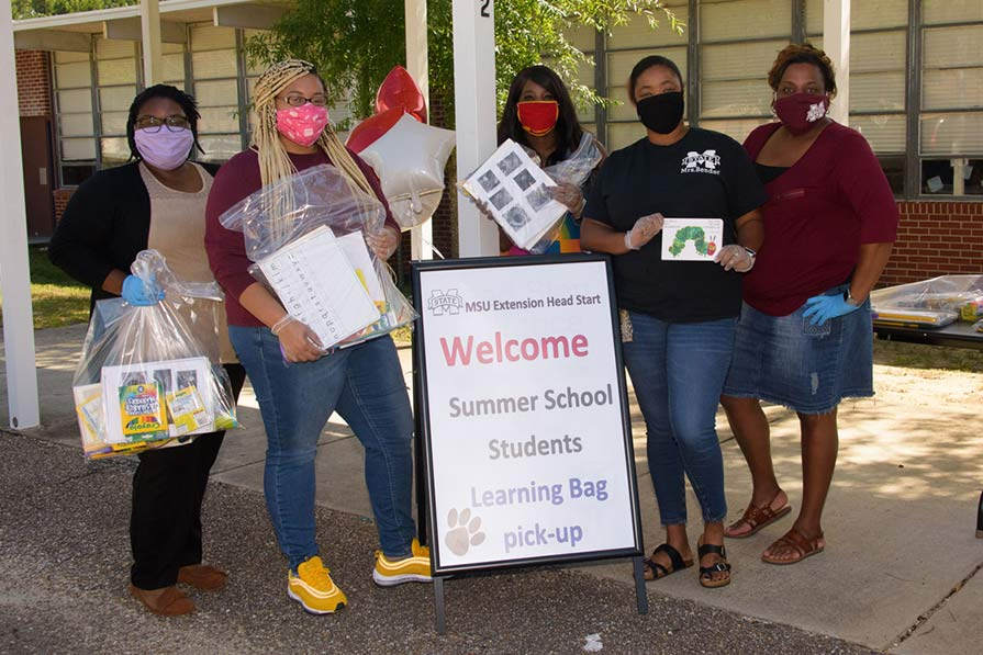 "Five women wearing maks and holding plastic bags filled with learning material stand behind a sign that says, ""Welcome Summer School Students Learning Bag pick-up."""