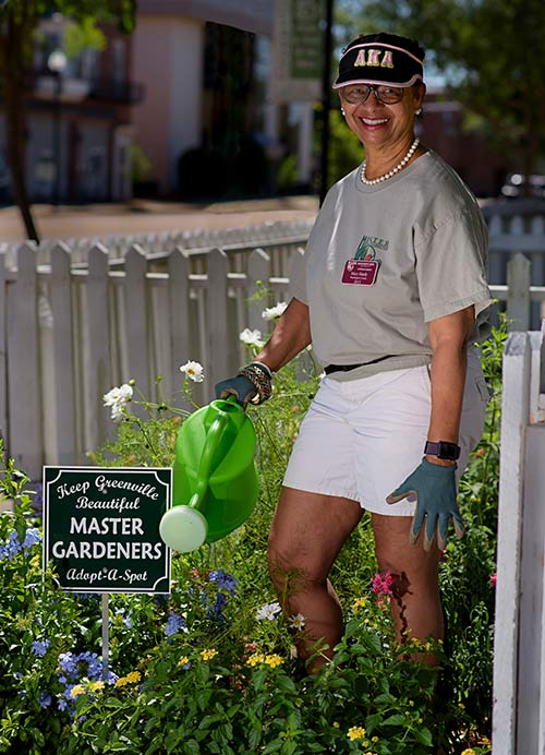 A woman stands next to a flower bed holding a green watering can.