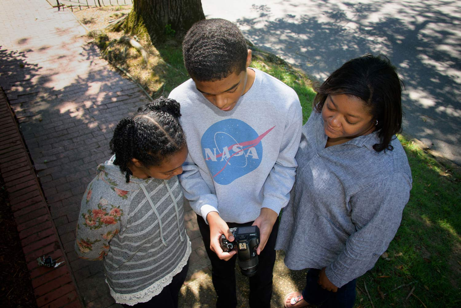 Overhead shot of a young boy holding a camera standing between two women.