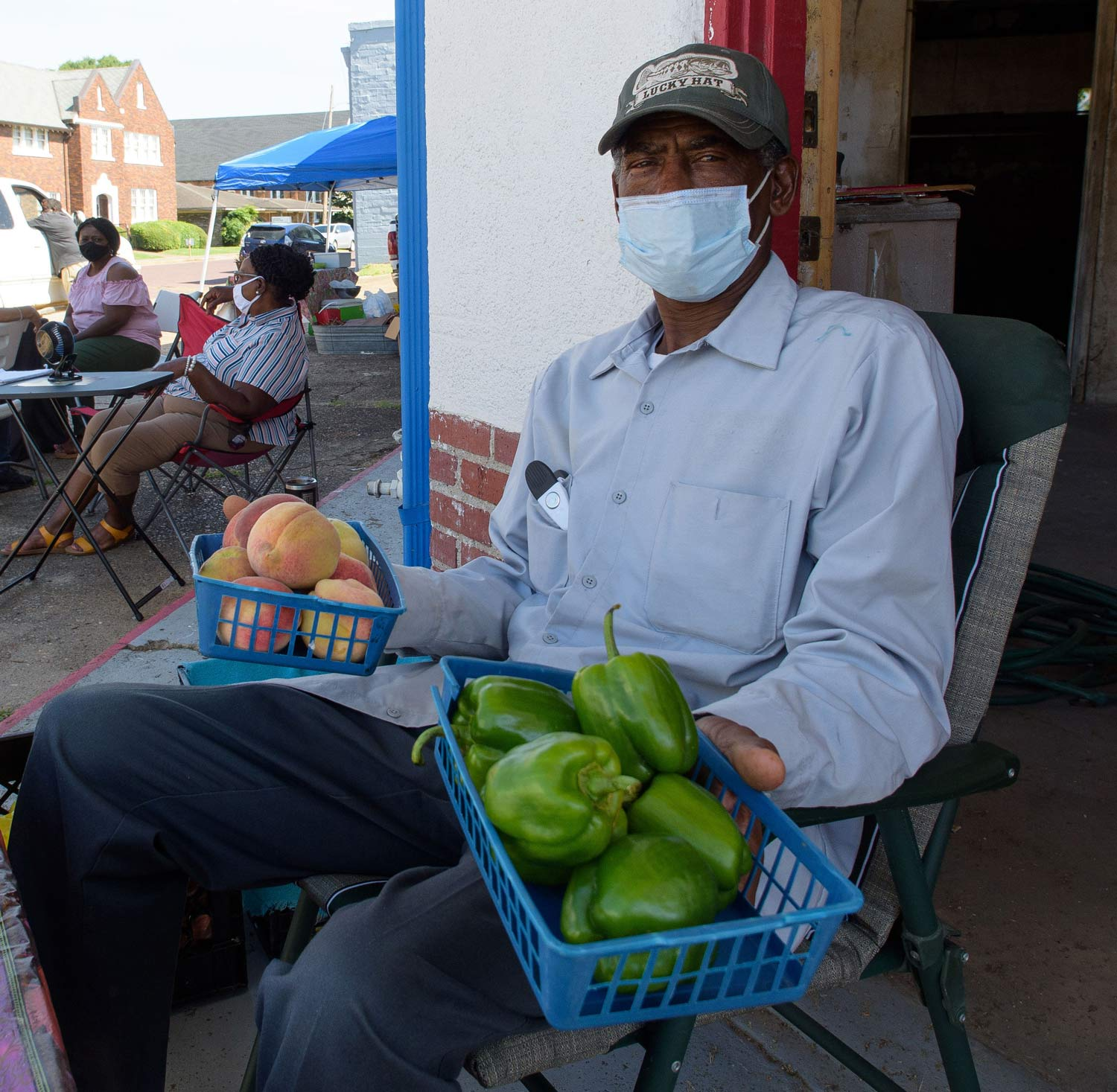A man wearing a mask holds two blue baskets filled with green bell peppers and peaches.