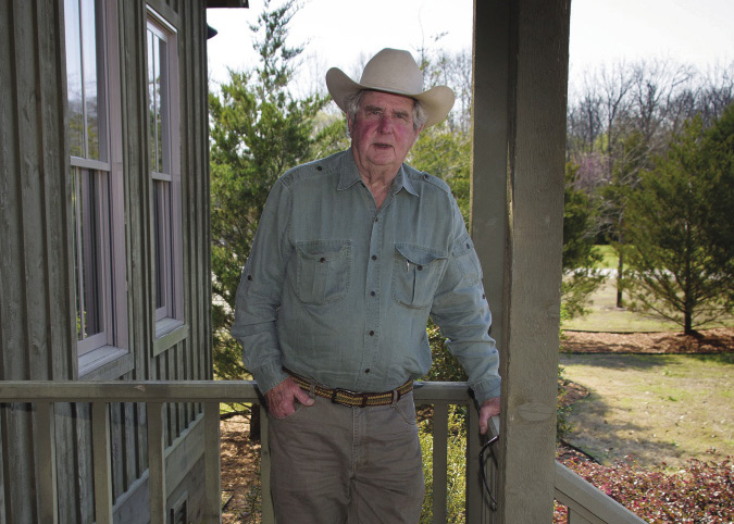 A man stands on a porch while leaning on the rail.