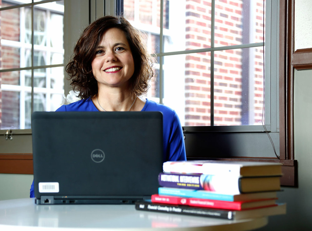 •	Lady sitting at desk with laptop and books