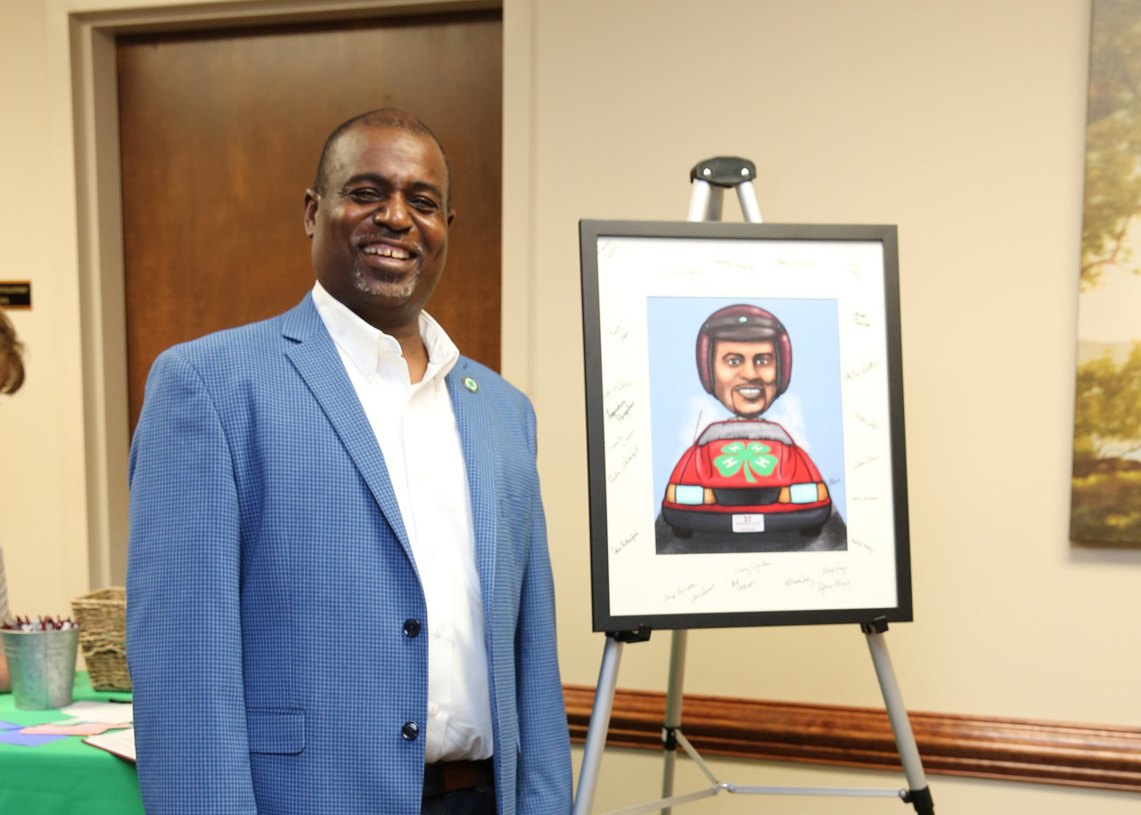 Larry Alexander stands beside a caricature of himself.