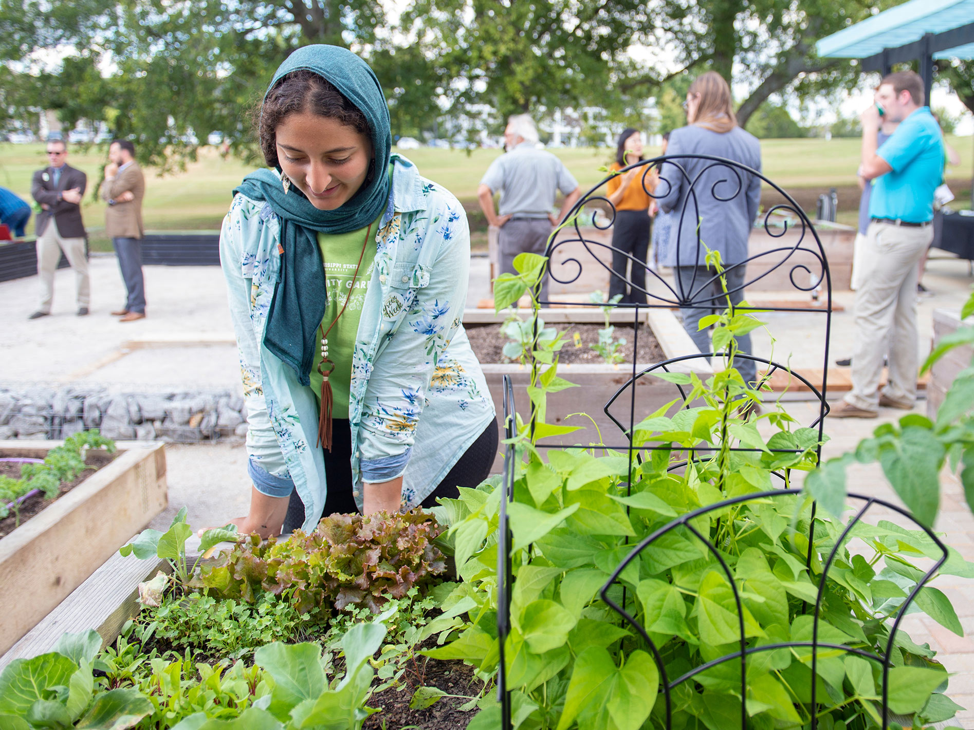 A woman with a teal scarf wrapped around her head leans toward a gardening box filled with bright green, leafy plants. Several other people stand conversing in the background.