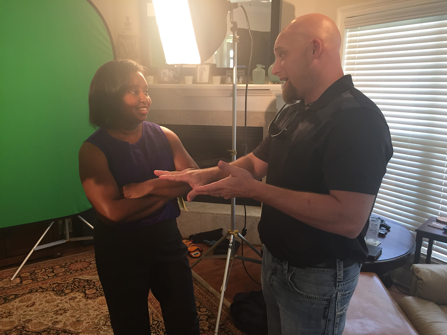 Host Natasha Haynes stands beside executive producer Brian Utley discussing the next shot.