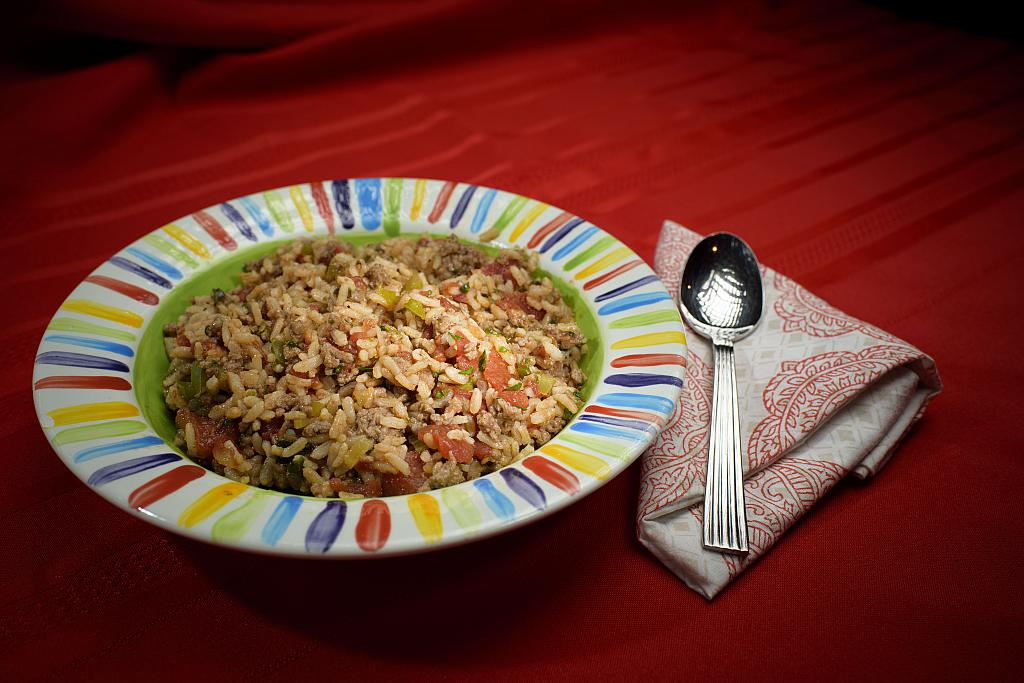 A bowl of Italian ground beef and rice in a rainbow-striped bowl sits on a red tablecloth with a red and white cloth napkin and a spoon.