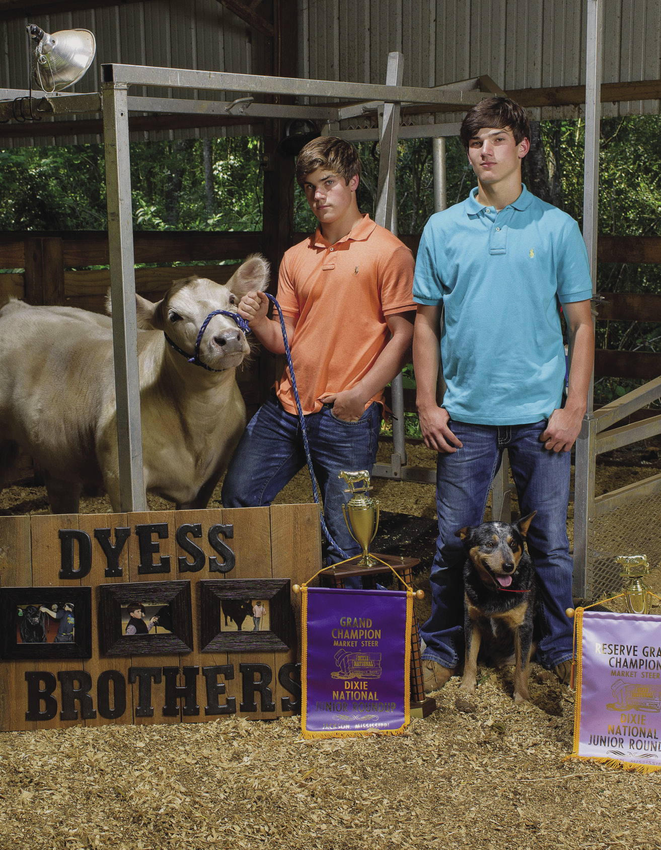 2 young men with a calf and a dog and Dixie National trophies.