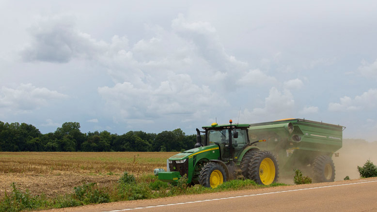 A tractor drives beside a crop