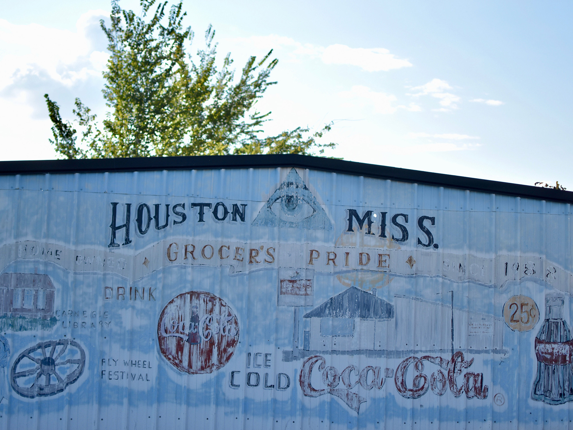 Photo of the side of a metal building that has been painted blue and has several different symbols and paintings.