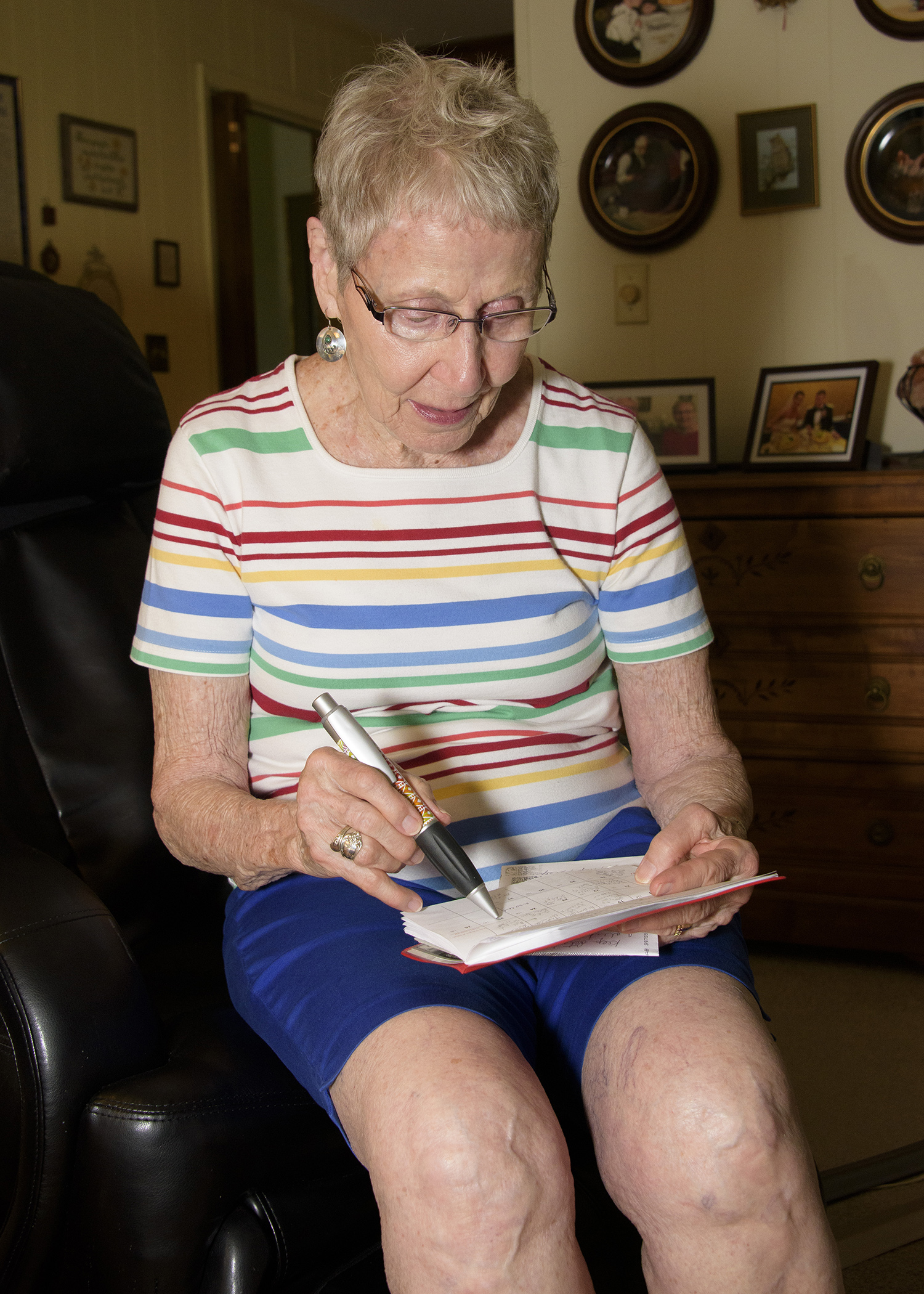 A gray-haired woman in blue shorts and a multi-colored striped shirt holds a pen over a pocket calendar to check appointments.