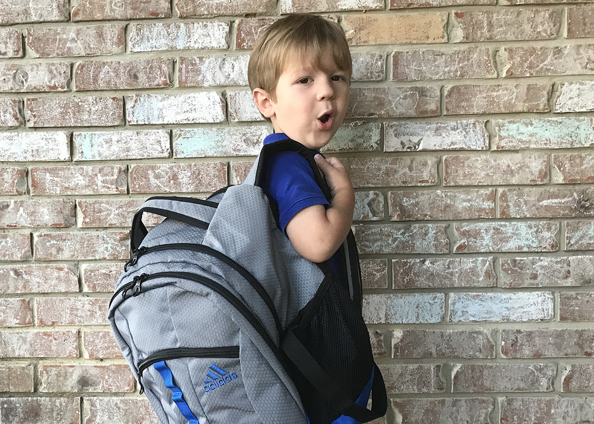 : Little boy wears backpack on one shoulder to demonstrate an incorrect way to carry it.