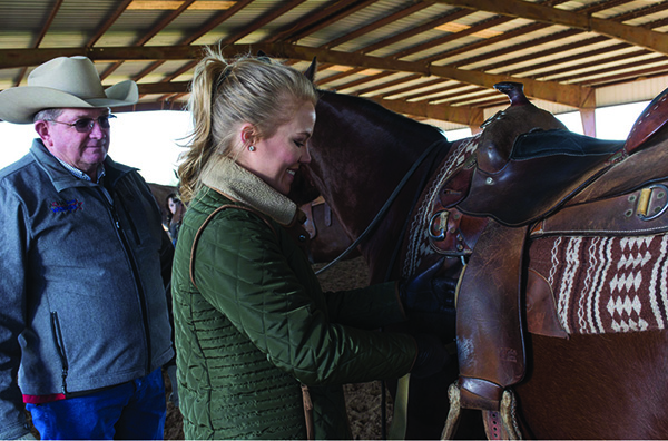 A 4-her prepares her saddle on a quarter horse while instructor watches.