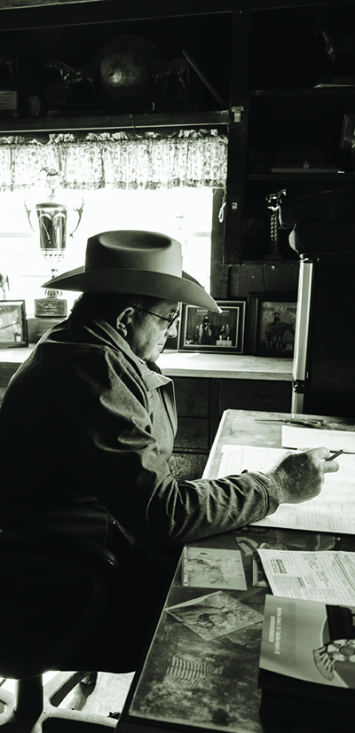 A man in cowboy hat sits at desk.