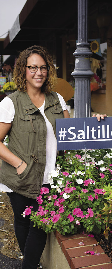 A woman stands on Main Street, beside a street lamp, holding a #Saltillo sign.