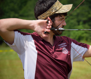 Young man pulling back on a bow.