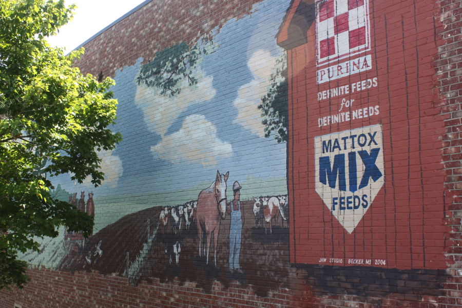 Painting on a brick wall of a building of an ad for Mattox Mix and a man and a horse are beside the ad.