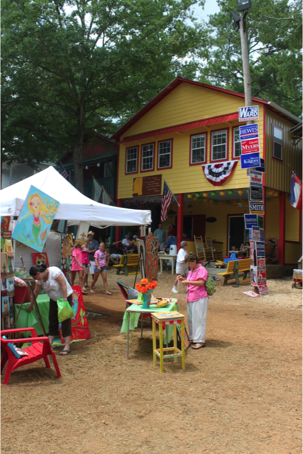 A yellow Neshoba County fair cabin stands in the back with a white tent and a lot of people walking and gathering in front of it.