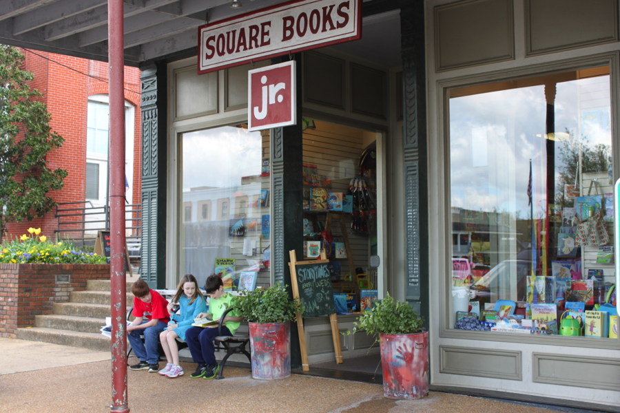 Three children gather in front of Square Books jr store.