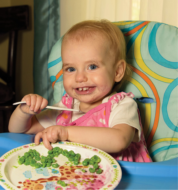 Smiling baby in high chair eating lunch.