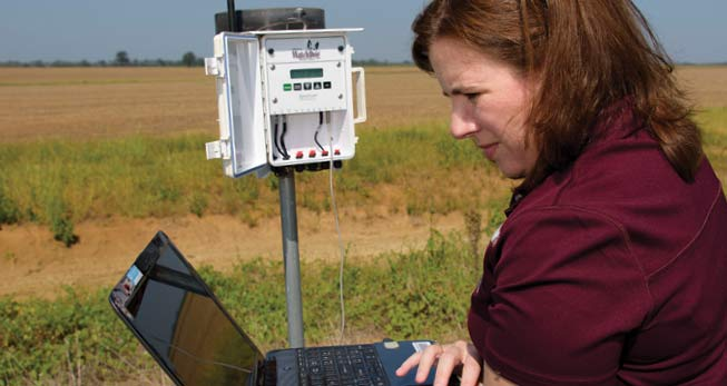 short sleeve maroon shirt, standing in field with equipment and laptop