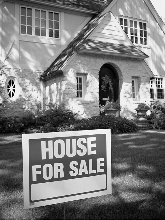 Image of a house with a for sale sign in the yard.