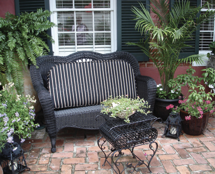 Bamboo palms and several other plants on an outdoor patio with a cushioned bench.