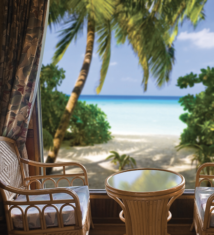 An indoor seating area looking out at a sandy beach.