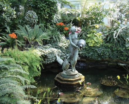 A garden pool with a statue in the center is lined with several green palms.