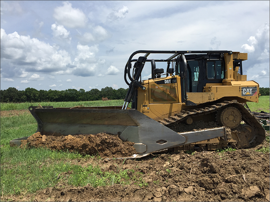 A bulldozer with a large attachment removes stems in a field.