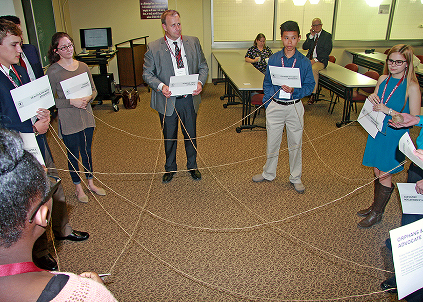 group of participants in a circle connected by string.