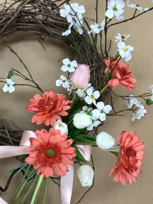 More pink and white flowers on grapevine wreath.