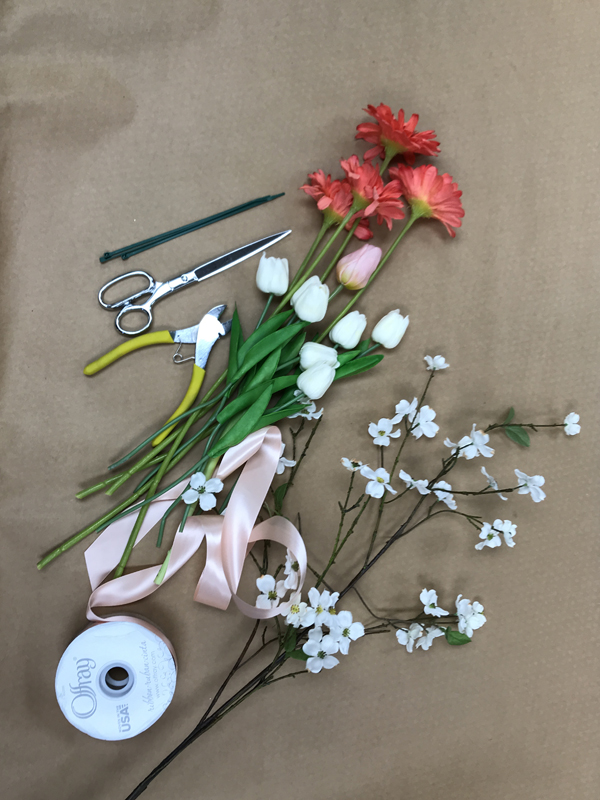 Materials for wreath laid out; pink ribbon, white flowers, scissors, and wire cutters.