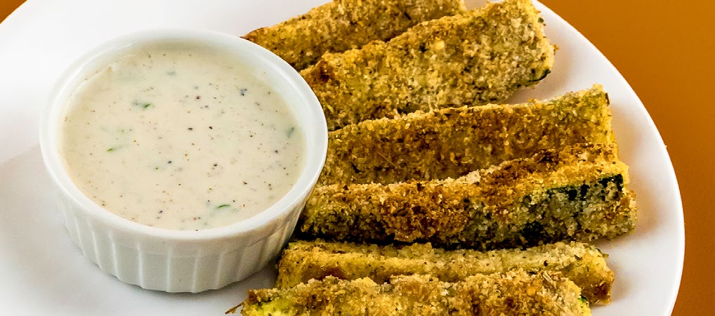A plate of breaded zucchini sticks and and small bowl of ranch dip.