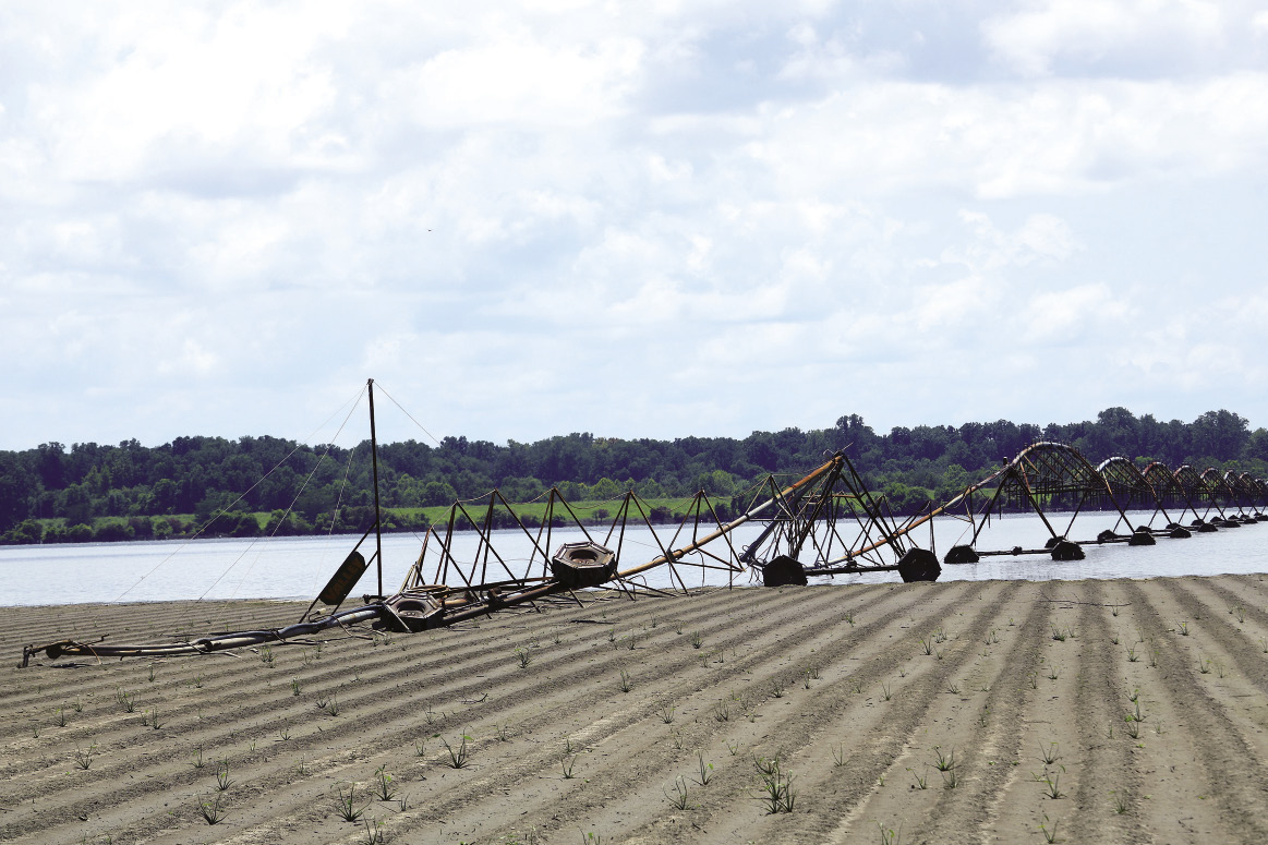 A partially flooded farm field contains damaged irrigation equipment.