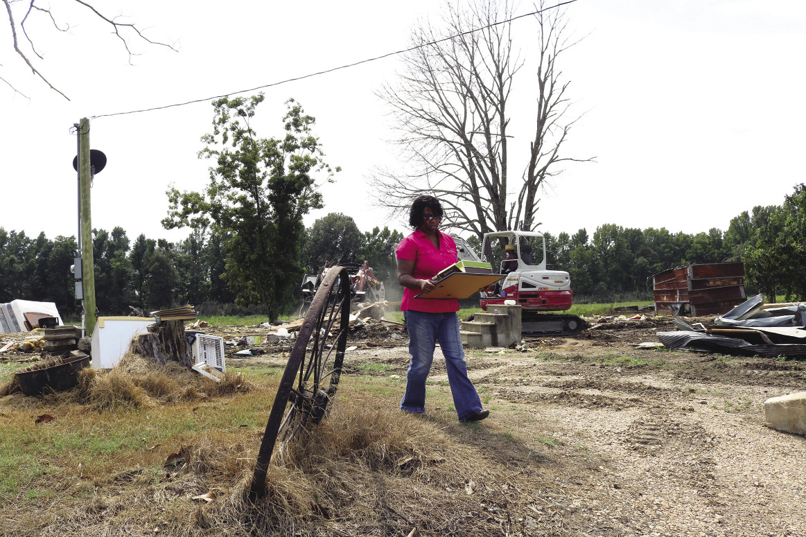 A woman carries some of her belongings at the site of a destroyed house. A piece of heavy equipment demolishes the house in the background.